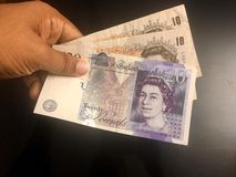 Paying in United Kingdom pound sterling currency notes. Paying in United Kingdom pound sterling currency royalty free stock photography