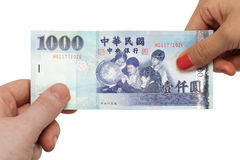 Paying up. A pair of hands exchanging a 1000 New Taiwan dollar bill Royalty Free Stock Photography