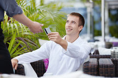 Payment. The young man gives the waiter a credit card Royalty Free Stock Photo