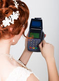 Payment card in a bank terminal. The concept of of electronic payment. Closeup of a beautiful bride holding credit card. Over payment terminal Royalty Free Stock Images