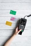 Payment card through terminal in store top view wooden background Royalty Free Stock Photos