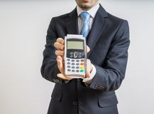 Payment with credit card. Businessman holds payment terminal in hand Stock Images