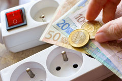 Payment for electricity in house - energy supply and power outlet. Euro coins and banknote Royalty Free Stock Photos