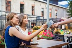 Young women paying for coffee at street cafe Royalty Free Stock Images