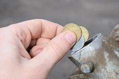 Payment for the gas, fuel, gasoline, diesel concept. Hand dropping money, coin in the can of fuel stock photography