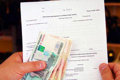 Payment of the invoice. Man holding money and a Russian tax return Royalty Free Stock Image