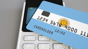 Payment or POS terminal with credit card featuring flag of Argentina. Argentinian retail commerce or banking system. Plastic bank card featuring flag and POS Stock Photo