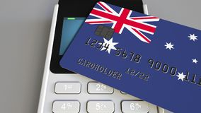 Payment or POS terminal with credit card featuring flag of Australia. Australian retail commerce or banking system. Plastic bank card featuring flag and POS Stock Images
