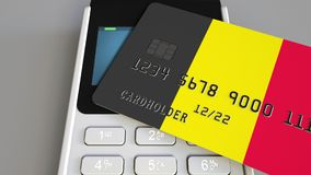 Payment or POS terminal with credit card featuring flag of Belgium. Belgian retail commerce or banking system conceptual. Plastic bank card featuring flag and Royalty Free Stock Photo