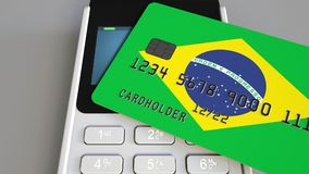 Payment or POS terminal with credit card featuring flag of Brazil. Brazilian retail commerce or banking system. Plastic bank card featuring flag and POS terminal Royalty Free Stock Photos