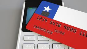 Payment or POS terminal with credit card featuring flag of Chile. Chilean retail commerce or banking system conceptual. Plastic bank card featuring flag and POS Stock Photos