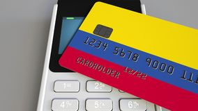 Payment or POS terminal with credit card featuring flag of Colombia. Colombian retail commerce or banking system. Plastic bank card featuring flag and POS Royalty Free Stock Photo