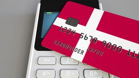 Payment or POS terminal with credit card featuring flag of Denmark. Danish retail commerce or banking system conceptual. Plastic bank card featuring flag and POS Royalty Free Stock Images
