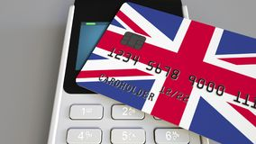 Payment or POS terminal with credit card featuring flag of Great Britain. British retail commerce or banking system. Plastic bank card featuring flag and POS Stock Images