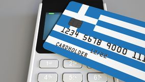 Payment or POS terminal with credit card featuring flag of Greece. Greek retail commerce or banking system conceptual 3D. Plastic bank card featuring flag and Stock Photo