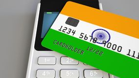 Payment or POS terminal with credit card featuring flag of India. Indian retail commerce or banking system conceptual 3D. Plastic bank card featuring flag and Royalty Free Stock Photos