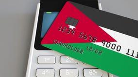 Payment or POS terminal with credit card featuring flag of Jordan. Jordanian retail commerce or banking system. Plastic bank card featuring flag and POS terminal Stock Photography