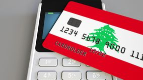 Payment or POS terminal with credit card featuring flag of Lebanon. Lebanese retail commerce or banking system. Plastic bank card featuring flag and POS terminal Stock Images