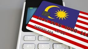 Payment or POS terminal with credit card featuring flag of Malaysia. Malaysian retail commerce or banking system. Plastic bank card featuring flag and POS Royalty Free Stock Image