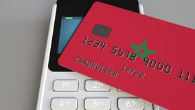 Payment or POS terminal with credit card featuring flag of Morocco. Moroccan retail commerce or banking system. Plastic bank card featuring flag and POS terminal Royalty Free Stock Images