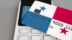 Payment or POS terminal with credit card featuring flag of Panama. Panamian retail commerce or banking system conceptual. Plastic bank card featuring flag and Stock Photography