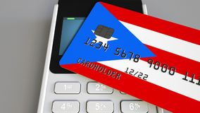 Payment or POS terminal with credit card featuring flag of Puerto Rico. Retail commerce or banking system conceptual 3D. Plastic bank card featuring flag and POS Stock Images