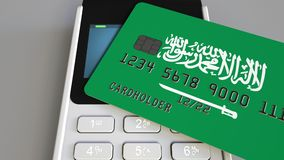 Payment or POS terminal with credit card featuring flag of Saudi Arabia. Retail commerce or banking system conceptual 3D. Plastic bank card featuring flag and Royalty Free Stock Image