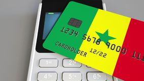 Payment or POS terminal with credit card featuring flag of Senegal. Senegalese retail commerce or banking system. Plastic bank card featuring flag and POS Stock Images