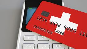 Payment or POS terminal with credit card featuring flag of Switzerland. Swiss retail commerce or banking system. Plastic bank card featuring flag and POS Stock Images