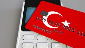 Payment or POS terminal with credit card featuring flag of Turkey. Turkish retail commerce or banking system conceptual. Plastic bank card featuring flag and POS royalty free stock photo