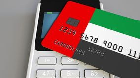 Payment or POS terminal with credit card featuring flag of the United Arab Emirates. UAE retail commerce or banking. Plastic bank card featuring flag and POS stock video