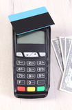 Payment terminal with contactless credit card and currencies dollar, cashless paying for shopping or products Royalty Free Stock Photography