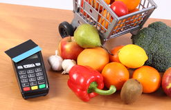 Payment terminal with contactless credit card, fruits and vegetables, cashless paying for shopping. Payment terminal, credit card reader with contactless credit Stock Image