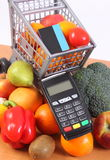 Payment terminal with contactless credit card, fruits and vegetables, cashless paying for shopping. Payment terminal, credit card reader with contactless credit Stock Photo