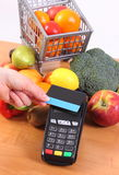 Payment terminal with contactless credit card and fruits and vegetables, cashless paying for shopping. Using payment terminal with contactless credit card and Royalty Free Stock Images