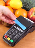 Payment terminal with contactless credit card and fruits and vegetables, cashless paying for shopping. Using credit card reader, payment terminal with Royalty Free Stock Image
