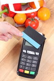Payment terminal with contactless credit card, fruits and vegetables, cashless paying for shopping Stock Photography