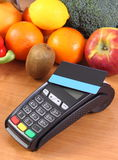 Payment terminal with contactless credit card, fruits and vegetables, concept of cashless paying for shopping. Payment terminal, credit card reader with Royalty Free Stock Images