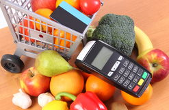 Payment terminal with contactless credit card, fruits and vegetables, concept of cashless paying for shopping. Payment terminal, credit card reader with Royalty Free Stock Photos