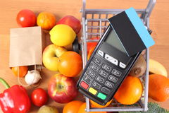 Payment terminal with contactless credit card, fruits and vegetables, concept of cashless paying for shopping. Payment terminal, credit card reader with Stock Photos