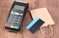 Payment terminal with contactless credit card and paper shopping bag, cashless paying for shopping Stock Photos
