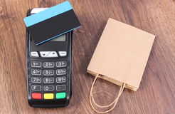 Payment terminal with contactless credit card and paper shopping bag, cashless paying for shopping Royalty Free Stock Photography