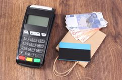 Payment terminal with credit card, currencies euro and paper shopping bag, concept of paying for shopping. Payment terminal with contactless credit card Stock Photo