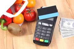 Payment terminal with credit card and dollar, fruits and vegetables, cashless paying for shopping. Credit card reader, payment terminal with contactless credit Stock Images