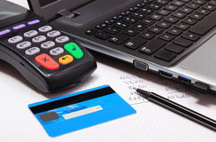 Payment terminal with credit card, laptop and financial calculations Royalty Free Stock Image