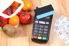 Payment terminal with credit card and polish currency, fruits and vegetables, cashless paying for shopping. Credit card reader, payment terminal with contactless Stock Photos