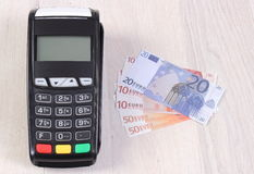 Payment terminal, credit card reader with currencies euro, cashless paying for shopping or products Royalty Free Stock Image