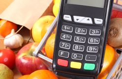 Payment terminal with fruits and vegetables, concept of cashless paying for shopping. Payment terminal, credit card reader and fresh fruits and vegetables with Royalty Free Stock Photography