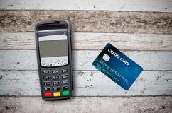 Payment terminal and credit card on wooden background Royalty Free Stock Photo