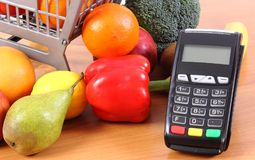 Payment terminal with fresh fruits and vegetables, cashless paying for shopping. Payment terminal, credit card reader and fresh fruits and vegetables with Royalty Free Stock Photos